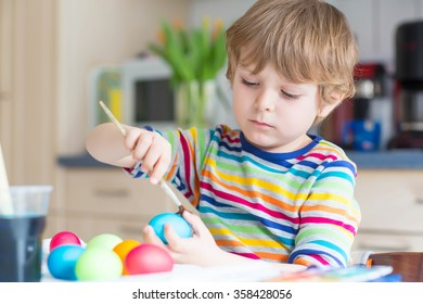 Funny little kid boy of 3 years coloring eggs for Easter holiday in domestic kitchen, indoors. Child having fun and celebrating feast.
