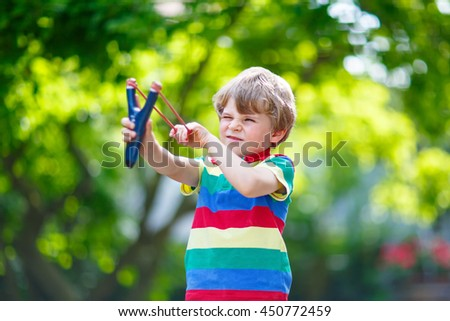 f5bb4016043 Funny little kid boy shooting wooden slingshot against green tree  background. Child having fun in
