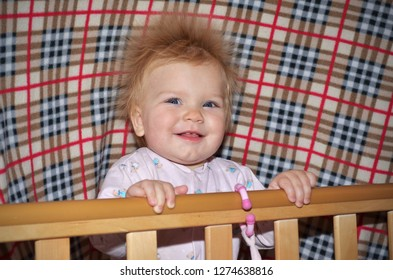 Funny little kid with electrified hair is smiling in the cradle.