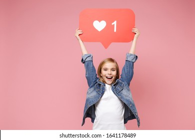 Funny little kid girl 12-13 years old in denim jacket isolated on pastel pink wall background in studio. Childhood lifestyle concept. Mock up copy space. Hold huge like sign from Instagram heart form