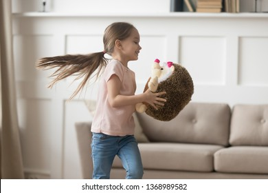 Funny little kid girl having fun holding fluffy stuffed toy animal standing in living room at home, creative preschool child playing with plush hedgehog, children imagination, leisure activity concept