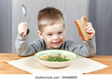 Funny little kid with plate of soup for dinner