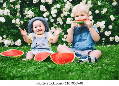 Funny little kids eating watermelon on green grass on nature at summer day. Brother and sister outdoors. Toddler Boy and Baby Girl. Children eat fruit at garden. Childhood, Family, Healthy Eating.