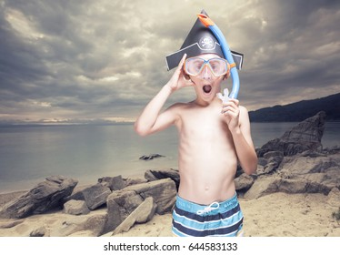 Funny little pirate with snorkeling mask on a deserted island