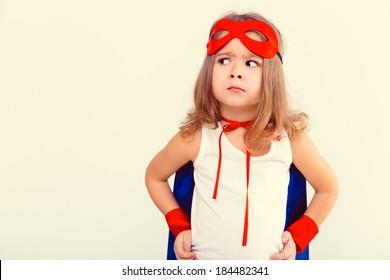 Funny little power super hero child (girl) in a blue raincoat. Superhero concept
