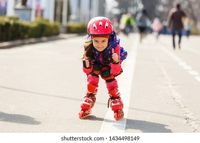 Funny Little pretty girl on roller skates in helmet riding in a park. Healthy lifestyle concept