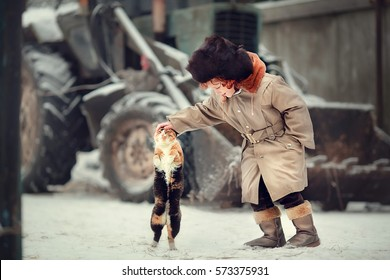 Funny little red-haired boy in earflaps hat is stroking a cat in the country in winter. Cat is standing on its hint legs as it is wanting so much to be stroked. Image with selective focus and toning.