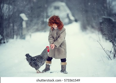 Funny little red-headed boy is feeding a rooster with a seed in the country in winter. Image with selective focus and toning.