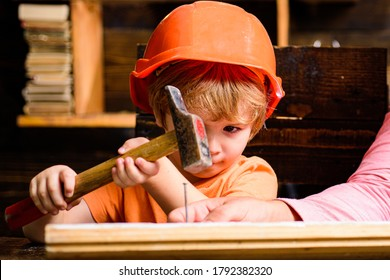 Funny little repairman with hammer. Kids construction worker. Child use a hammer to nail