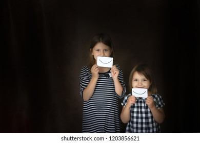 Funny little sister girls with paper emotions, the concept of emotion and childhood