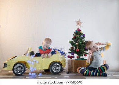 Funny little smiling kids driving toy car with Christmas tree. Happy child in colour fashion clothes bringing hewed xmas tree from snowy forest. Boys having fun at home. Family, tradition, holiday