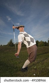 Funny looking golfer stretches before swing from the rough.