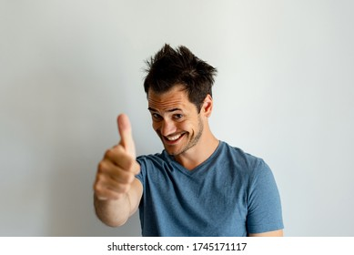 Funny looking young man with messy hair, gesturing the thumbes up sign, smiling natural.