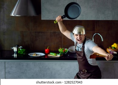 Funny loser man male with metal pan on head frying pan and wooden kitchen utensils in pose of ninja trying to cook failed and yell on grey modern loft kitchen. Unsuccessful bachelor on kitchen concept