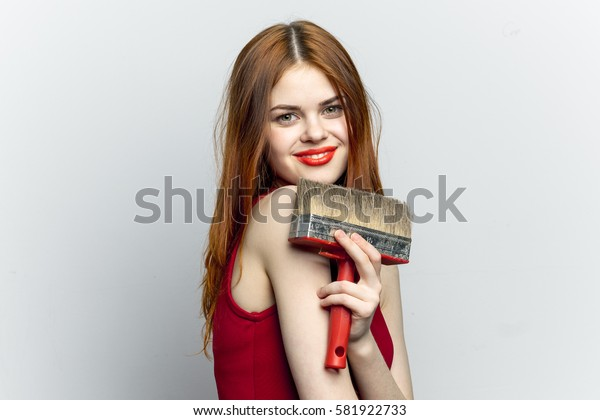 Funny lovely woman with brush for paint repairs, light background