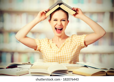 funny mad  girl student with glasses shouts with books in the library