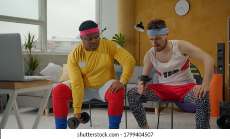 Funny male couple of fitness jerks engaged in sports, watching online training on laptop, trying to train biceps with heavy dumbbells. Fake sports. Comedy concept.