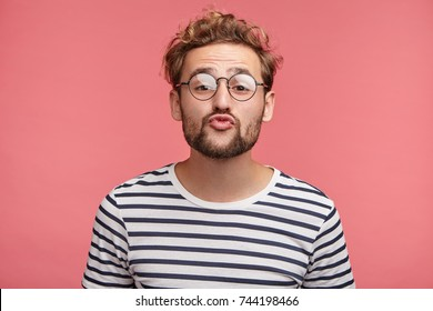 Funny male with curly trendy hairstyle, rounds lips as going to kiss someone, looks in anticipation, isolated over pink background. Fashionable bearded man epresses positive emotions, makes grimace