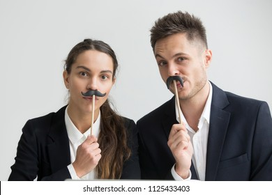 Funny male and female colleagues in suits holding fake mustache, businessman and businesswoman making silly faces, millennial coworkers grimacing looking at camera, creative team head shot portrait