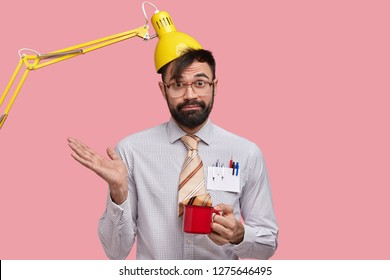 Funny male student has clueless expression, spreads palm, has doubtful expression, keeps lamp on head as hat, drinks fresh coffee, foolishes ater long hours working, dressed in formal outfit