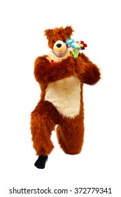 Funny man in bear costume with bouquet of toy flowers on white background