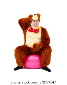 Funny man in bear costume on fitness ball isolated