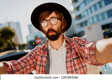 Funny man with beard making self portrait by camera while he traveling in big modern city in Asia.