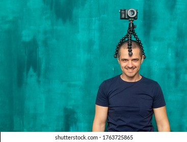 Funny man blogger, photogapher and videographer with camera on his head