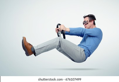 Funny man in blue t-shirt and goggles drives a car with steering wheel