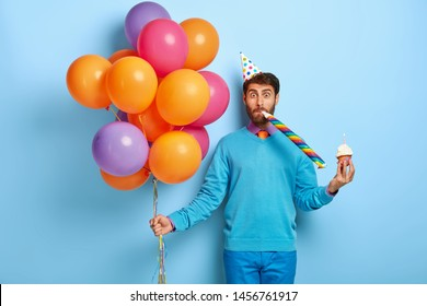 Funny man with bristle, wears party hat, blows horn, holds sweet muffin with burning candle, holds bunch of multicolored balloons, going to have birthday celebration, isolated on blue background