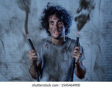 Funny man with burns and smoke holding electrical cable after getting a electric shock at home. Sad husband with dirty burnt face guilty expression. Domestic accidents, DYI and Electricity danger.