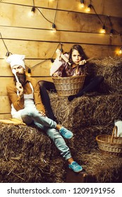 Funny man chef cook or baker with beard and moustache in hat toque and cute girl cookee teenager in apron sit on straw bales on rustic background.