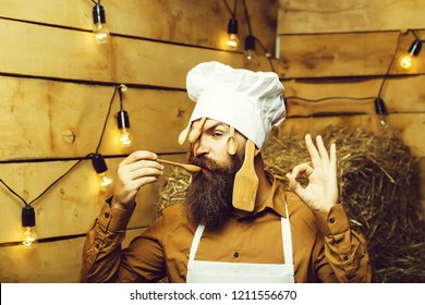Funny man chef cook or baker with beard and moustache in hat toque with wooden spoons and ok hand gesture stands on straw bales on rustic background.