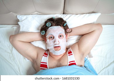 Funny man with a cosmetic mask on his face does spa treatment, relaxes in a room at home, with big, scared eyes open