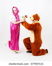 Funny man in costume of bear and girl from fairy tale posing