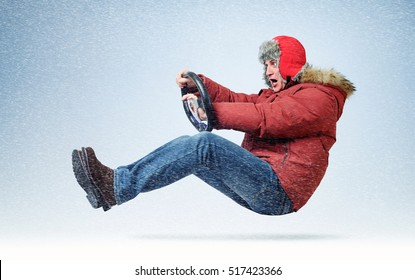 Funny man driver car in winter clothes with steering wheel. Flight through the snow concept