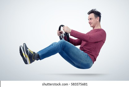Funny man drives a car with a steering wheel