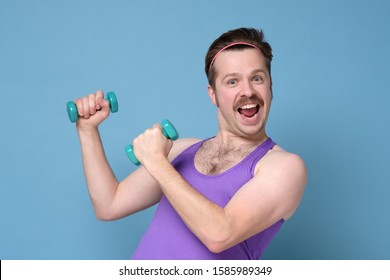 Funny man exercising and doing sport training. Humorous athletic man using small dumbbells for bodybuilding. Studio shot.