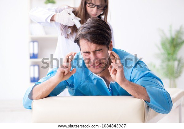 Funny man getting ready for buttocks syringe shot