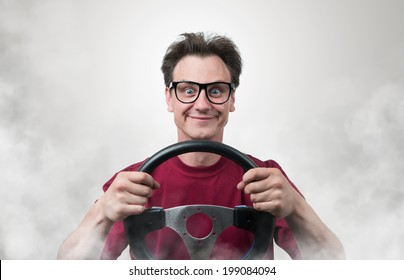 Funny man in glasses with a steering wheel in smoke