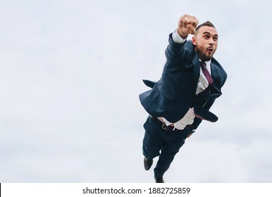 Funny man, groom, businessman flies in a blue suit with an open mouth, his hand outstretched forward. Rush to work. Cool photo with humor.