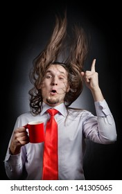 Funny man with hair up holding red mug and pointing up at black background