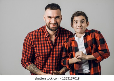 funny man and his kid has done something and they don't want to tell about it to their mother. close up shot. isolated grey background.embarrased dad and boy in checked red shirts