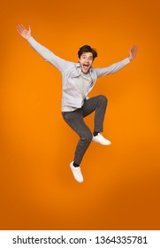 Funny man jumping with raised arms over orange studio background