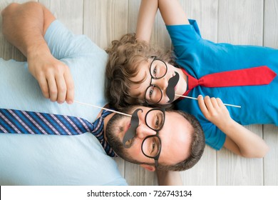 Funny man and kid with fake mustache. Happy family playing in home