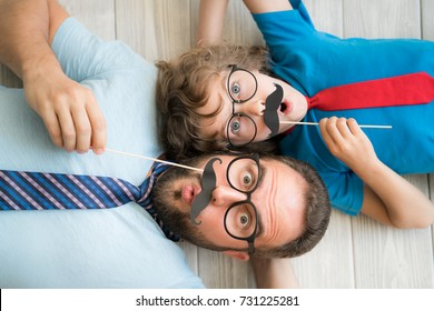 Funny man and kid with fake mustache. Happy family playing in home. Movember concept