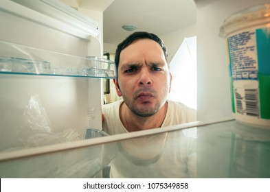 Funny man looking into the fridge
