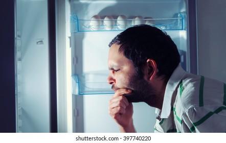 funny man looking into refrigerator