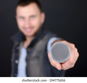 Funny man with microphone singing karaoke isolated on a black background