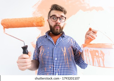 Funny man painting interior wall with paint roller in new house. Guy with roller applying paint on a wall.